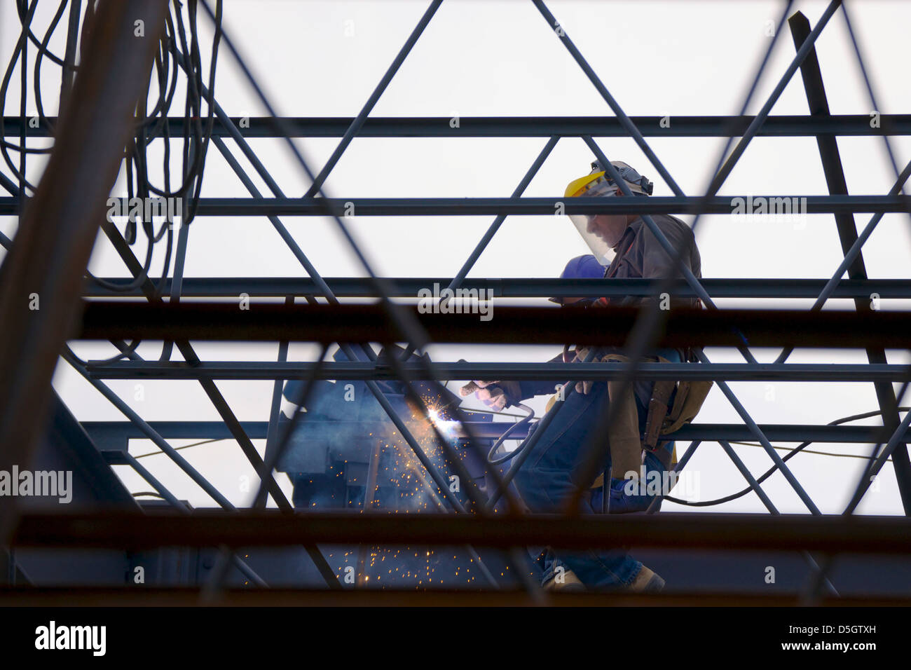 Ironworkers welding the steel framework of a building Stock Photo