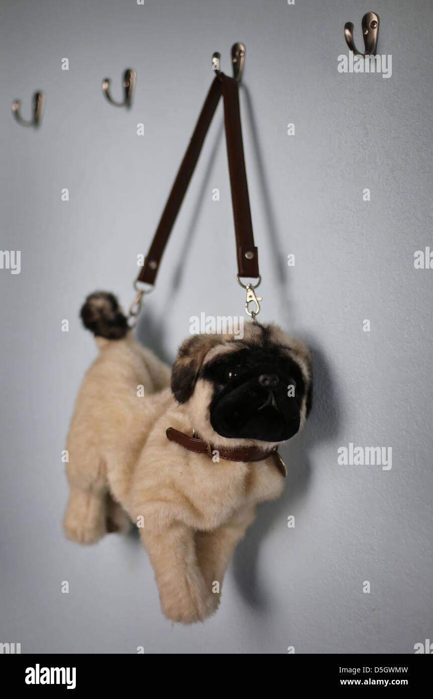 A pug shaped purse hanging on a hook. - Stock Image