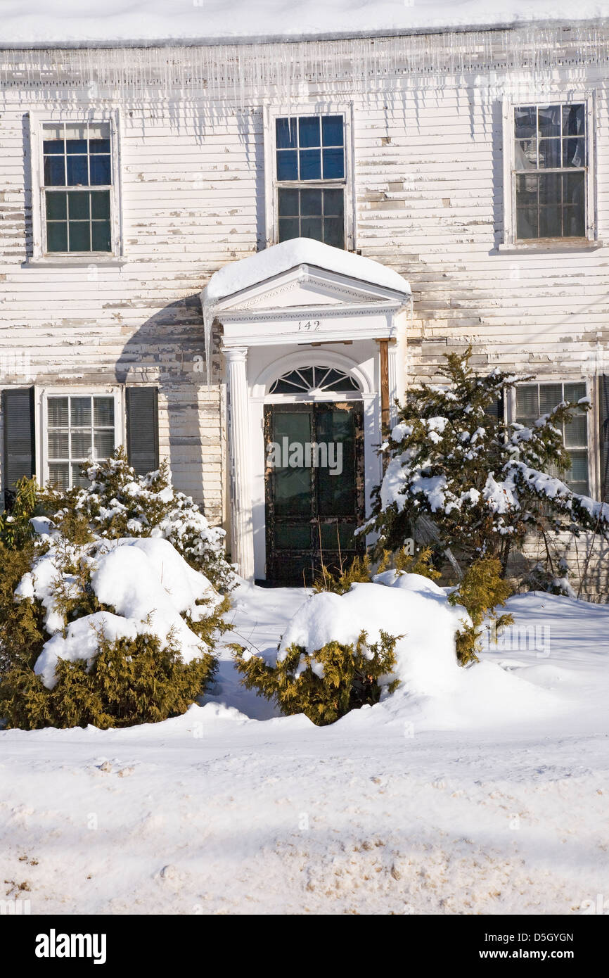 Rundown haunted home with snow and ice cycles, Ma., New England, USA - Stock Image
