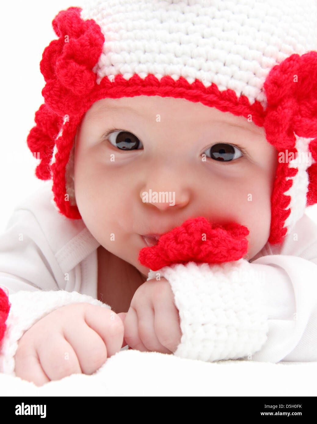 baby with knitted white hat baby on stomach - Stock Image