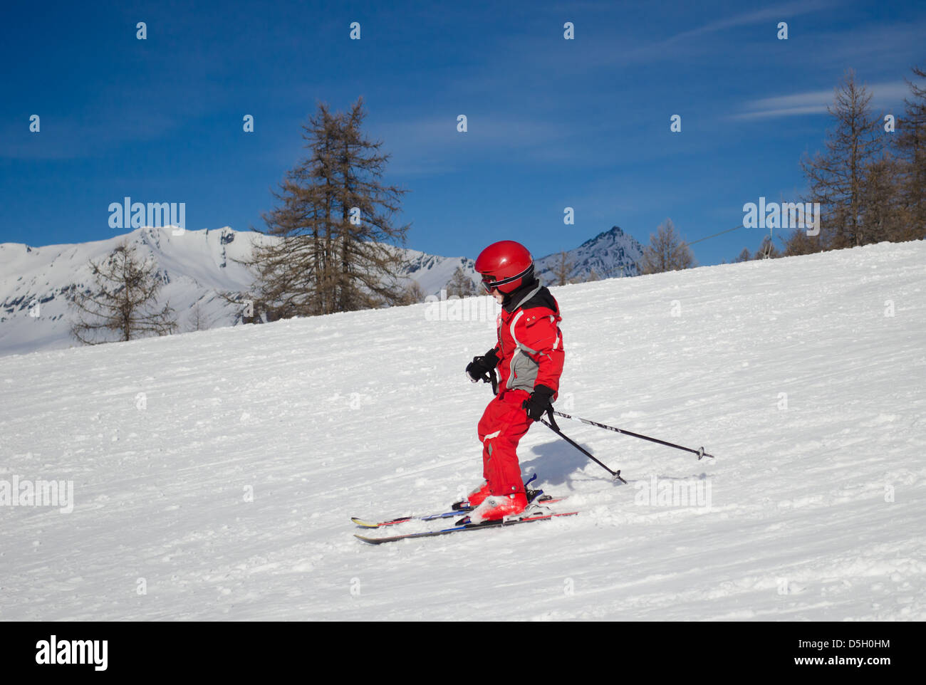 A kid in red ski suit skiing in a sunny day - Stock Image