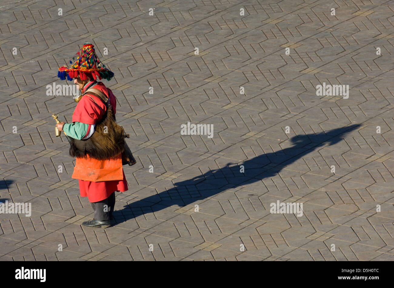 Traditional water-carrier dressed in red in the Djemaa el-Fna square, Marrakech, Morocco - Stock Image
