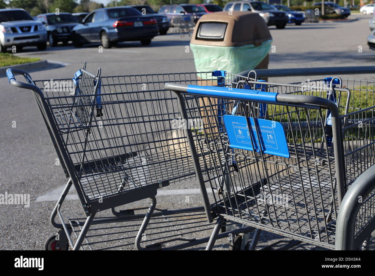 Shopping carts and a garbage can in a Walmart parking lot in the USA - Stock Image