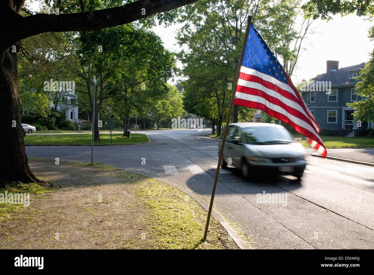 American Flag flies over speeding car in historic Lexington, MA on Memorial Day, 2011 - Stock Image