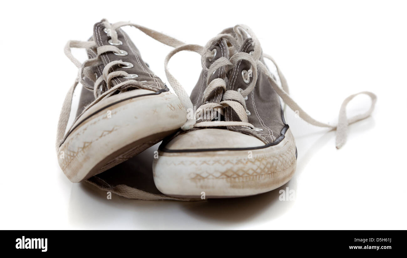 a pair of worn out gray retro sneakers on a white background - Stock Image