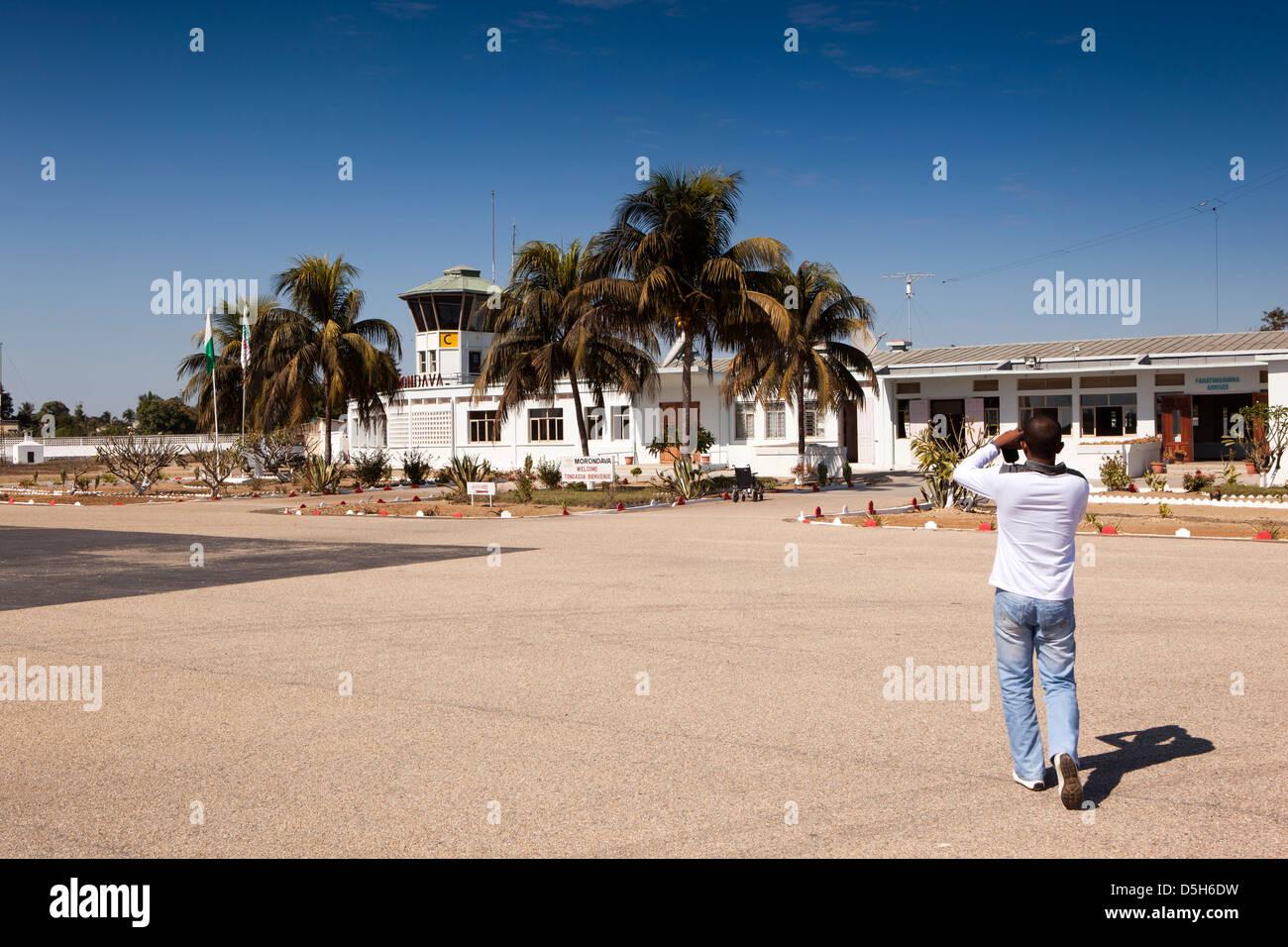 Madagascar, Morondava Airport, airside tourist photographing terminal building on tarmac apron - Stock Image