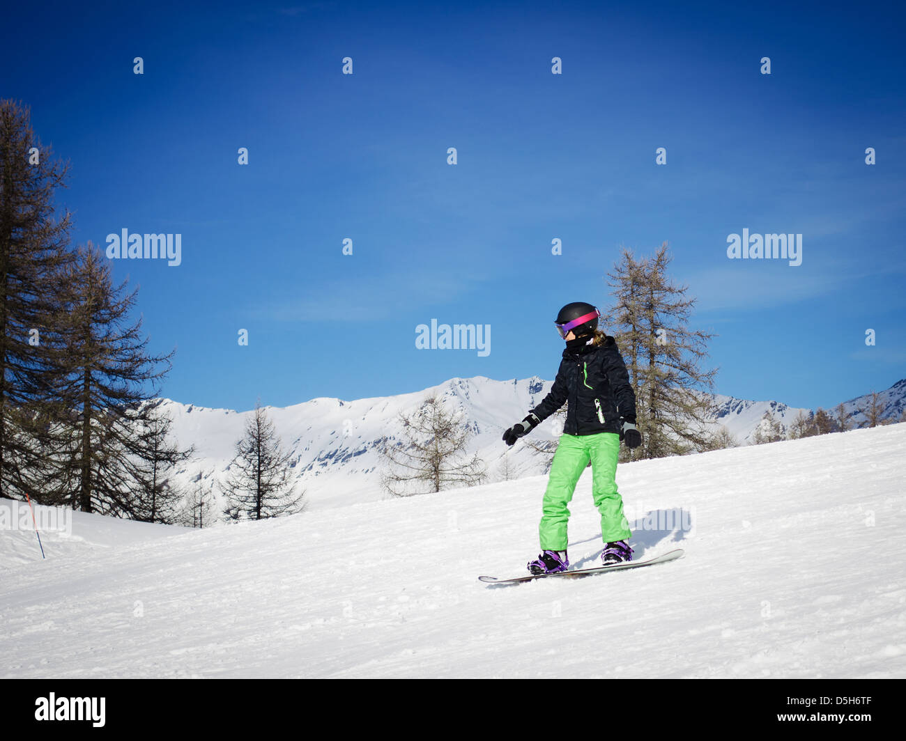 A girl or woman in green ski suit snowboarding in a sunny day - Stock Image