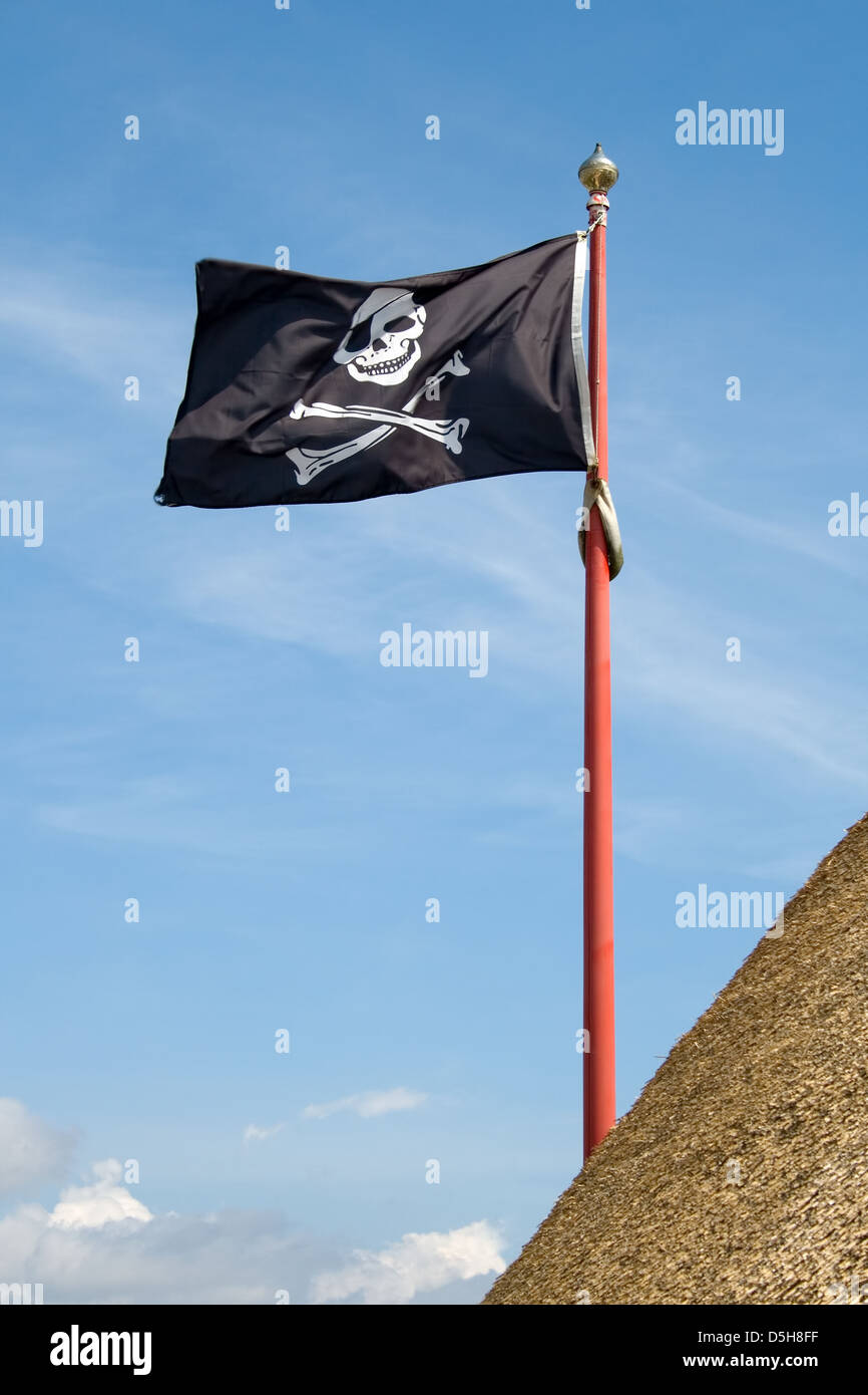 jolly roger pirate flag with a skull and crossbones on a blue sky background - Stock Image