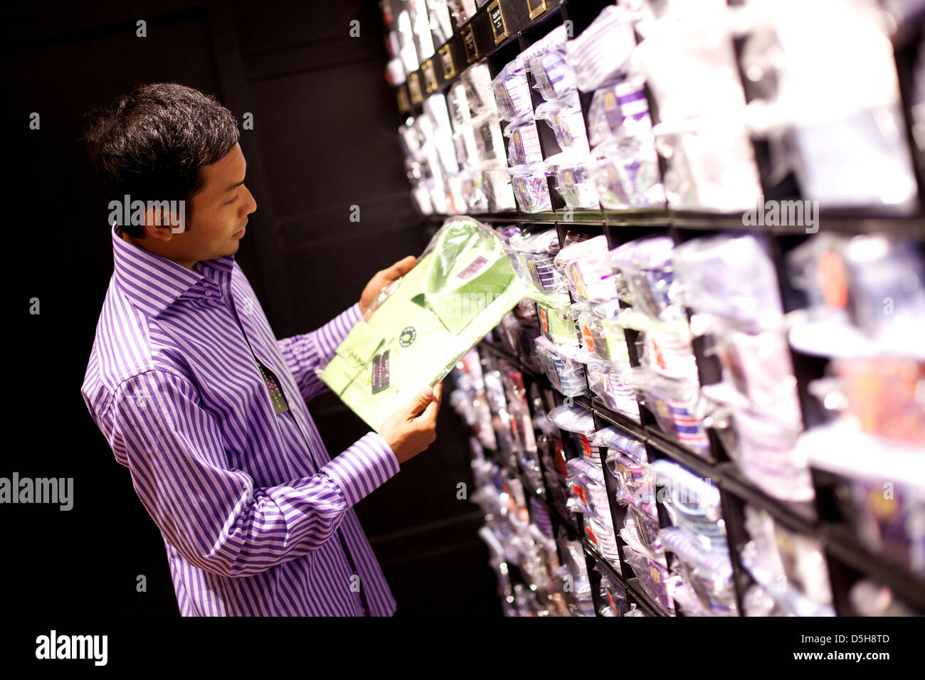 young man shopping in high street store - Stock Image