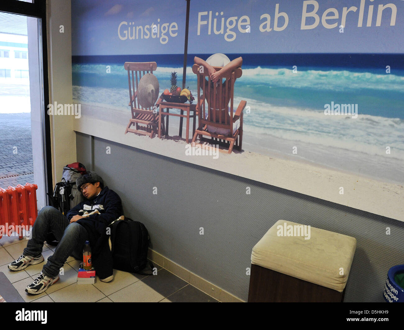 A Brazilian tourist sleeps below a poster with the inscription 'Low priced flights from Berlin' ('Guenstige - Stock Image
