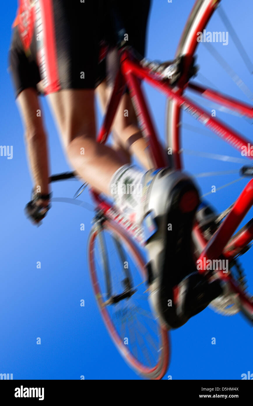racing cycle from behind in dynamic angle and blue background, use as background image with text and logos on it - Stock Image