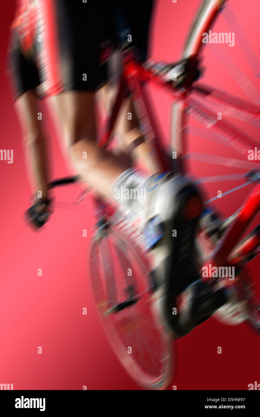 racing cycle from behind in dynamic angle and red background, use as background image with text and logos on it - Stock Image