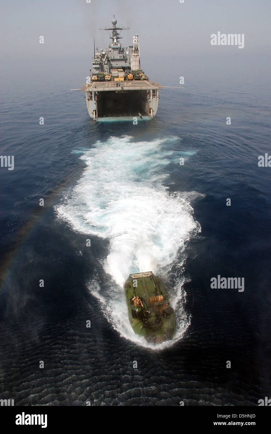 A US Navy amphibious assault vehicle departs the well deck of the amphibious dock landing ship USS Rushmore during Stock Photo