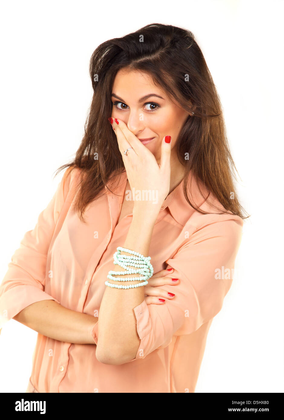 Portrait of a beautiful woman in a studio covering her mouth with her hand - Stock Image