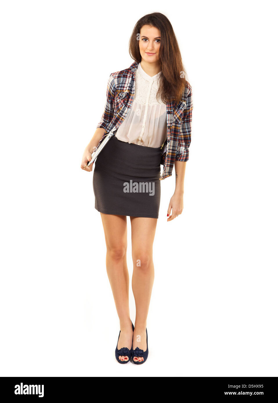 Full length of a beautiful college student with laptop standing against the white background Stock Photo