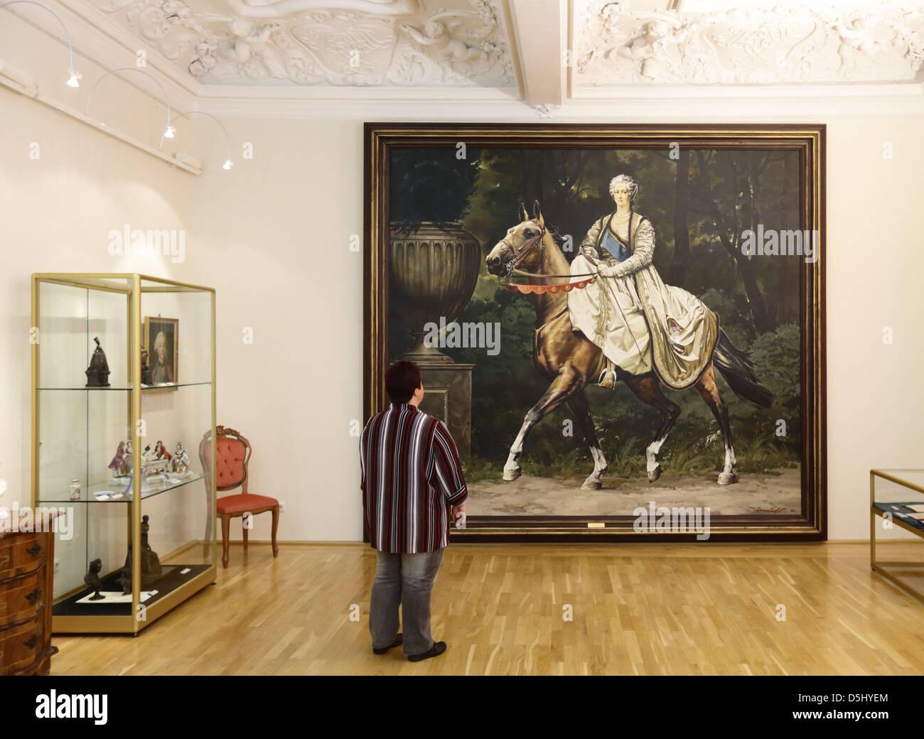 "A woman stands in front of a painting of the ""Catherine the Great"" route stands near a monument to the tsar in Zerbst, Stock Photo"