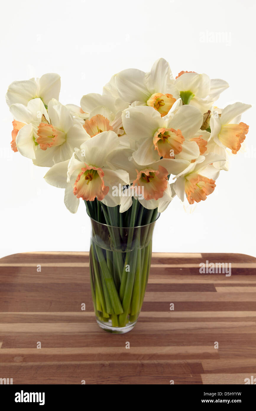 Daffodils in a glass vase on a oak worktop with a plain background. - Stock Image