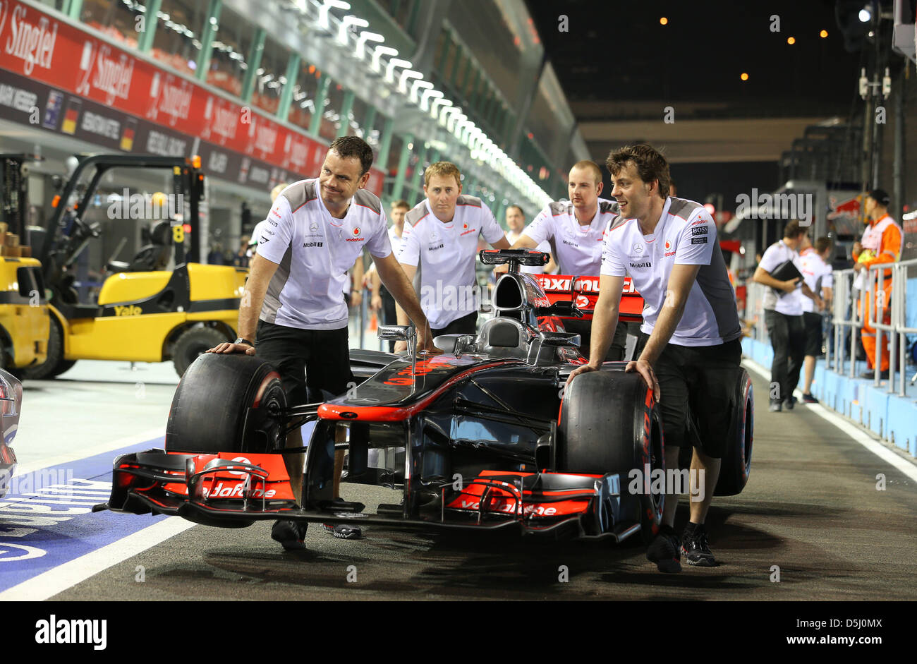 8dedd71c656 Mechanic of British Formula One driver Jenson Button of McLaren Mercedes  push the race car through
