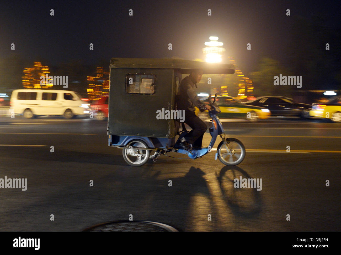 A man rides on a tricycle through busy evening traffic in Bejing, China, 11 October 2012. Photo: Rainer Jensen - Stock Image