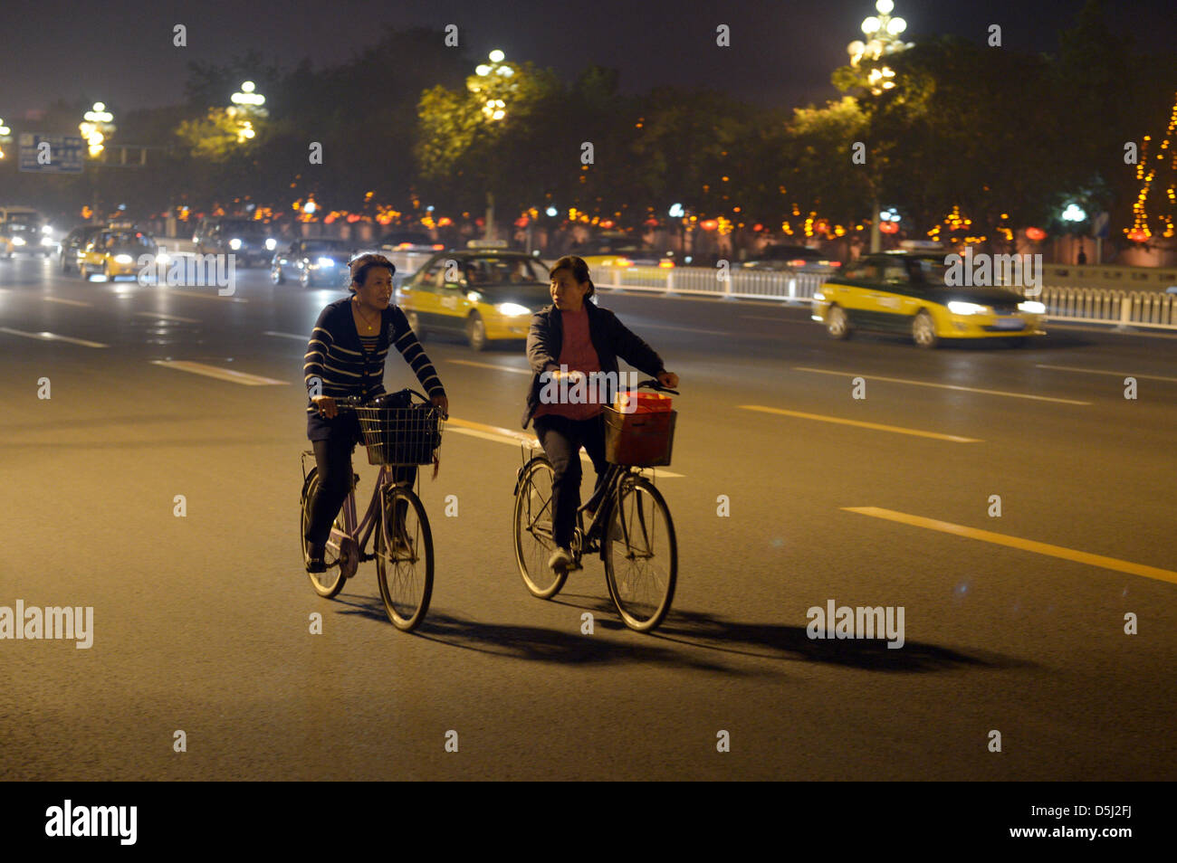 Two female cylcists ride on their bicycle through busy evening traffic in Bejing, China, 11 October 2012. Photo: - Stock Image