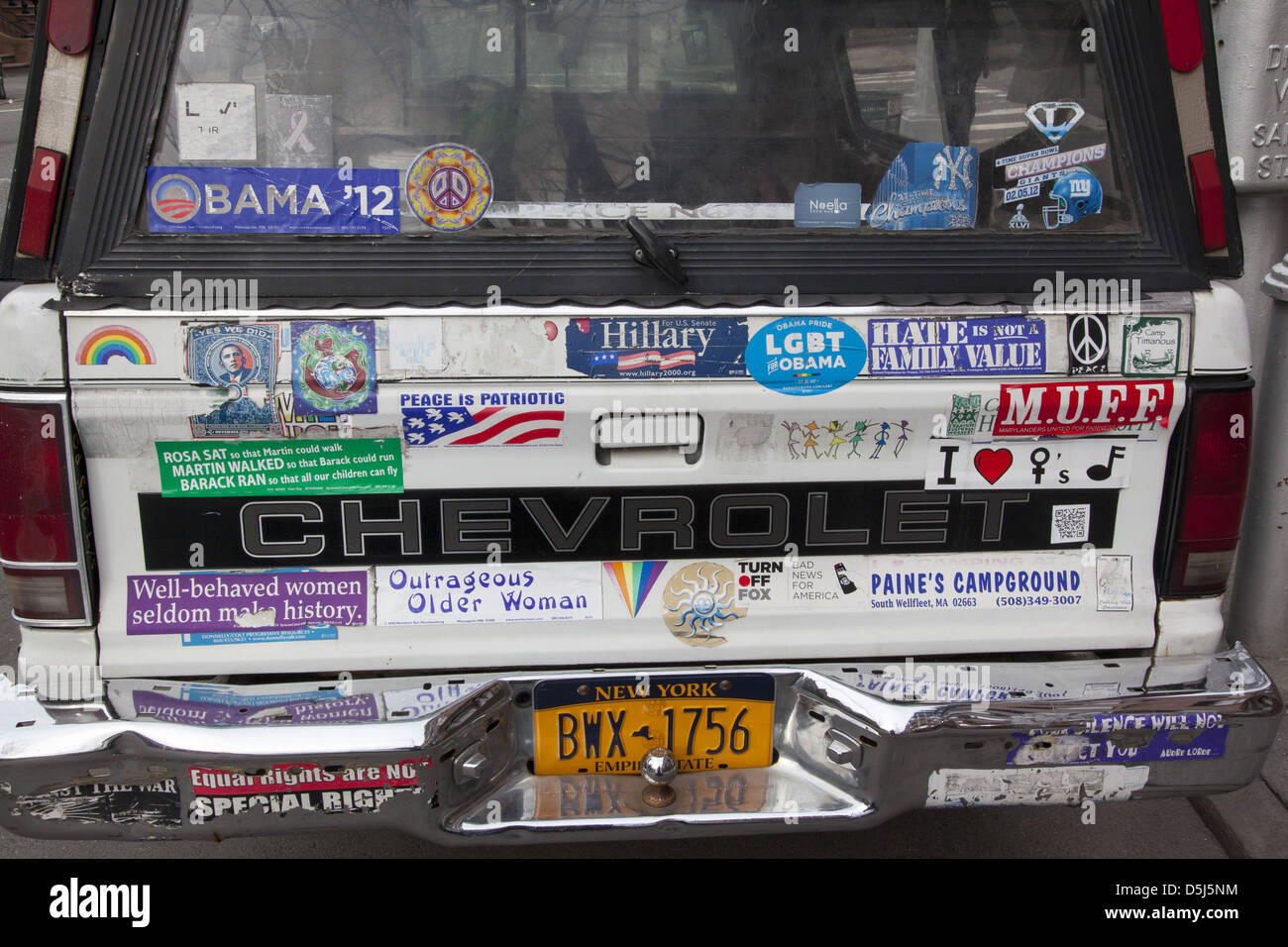 Bumper stickers on the rear end of a minivan parked in brooklyn ny