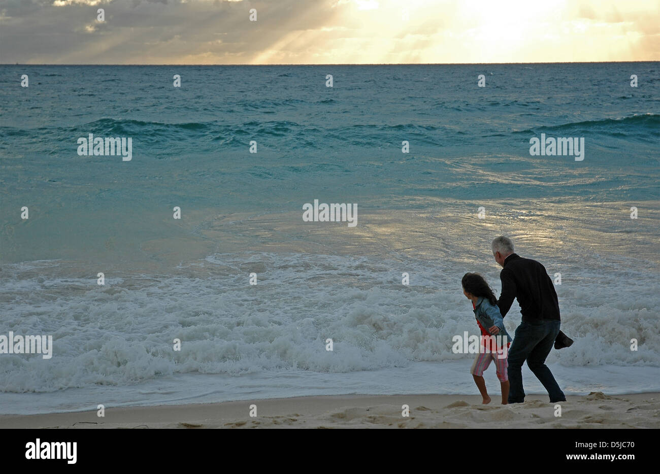 Father and daughter dodging waves at sunset. - Stock Image