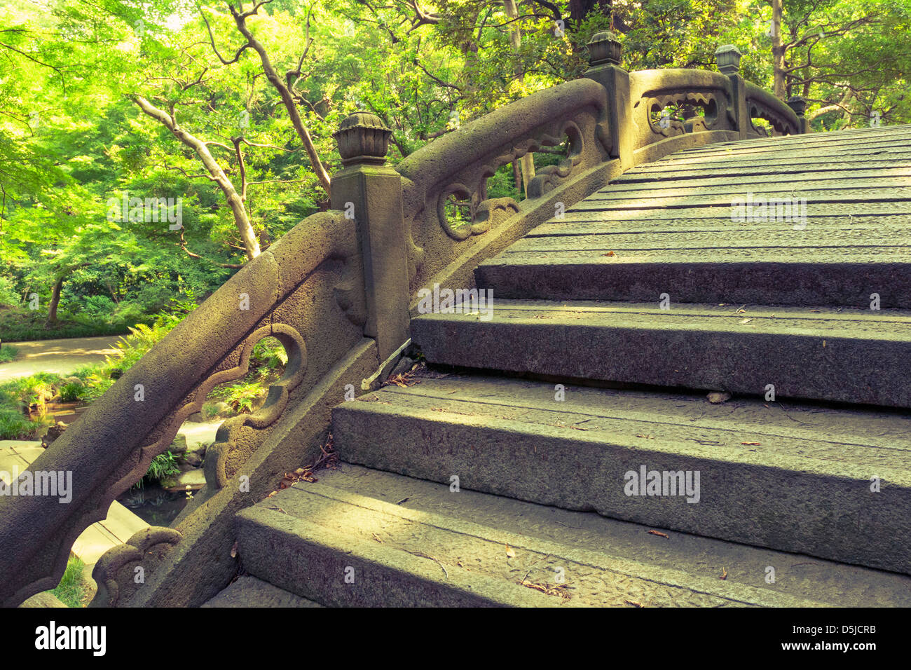 stone humpbacked bridge fragment with carved handrails in Japanese zen garden - Stock Image