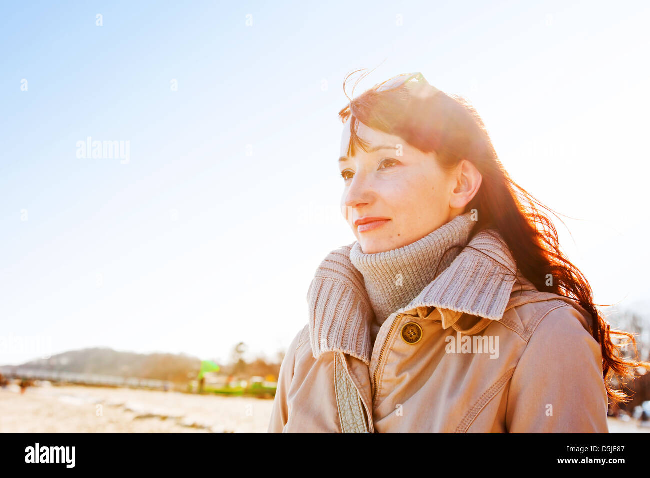 Beautiful young woman outdoors in winter sunshine by the coast - Stock Image