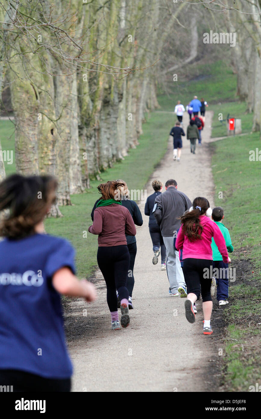 A group of runners participate in a 5km at a London Park. It's promoted by a worldwide organization called Parkrun. - Stock Image