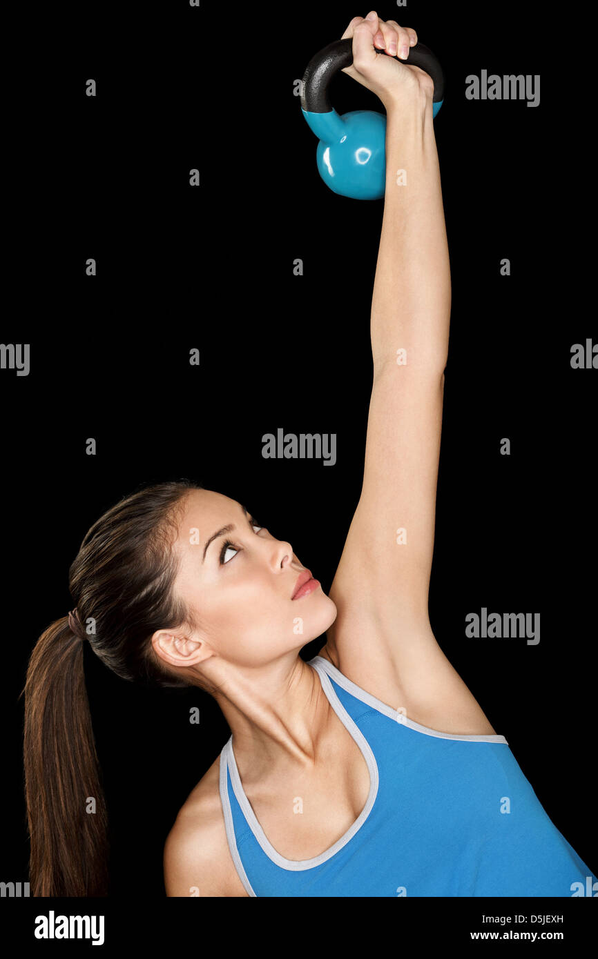 Beautiful multicultural woman training crossfit with kettlebell isolated on black background - Stock Image