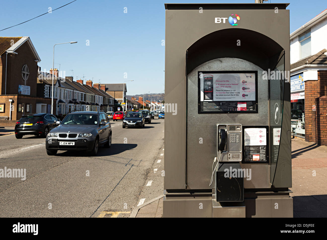 Open telephone kiosk alongside busy noisy road, Cardiff, Wales, UK - Stock Image