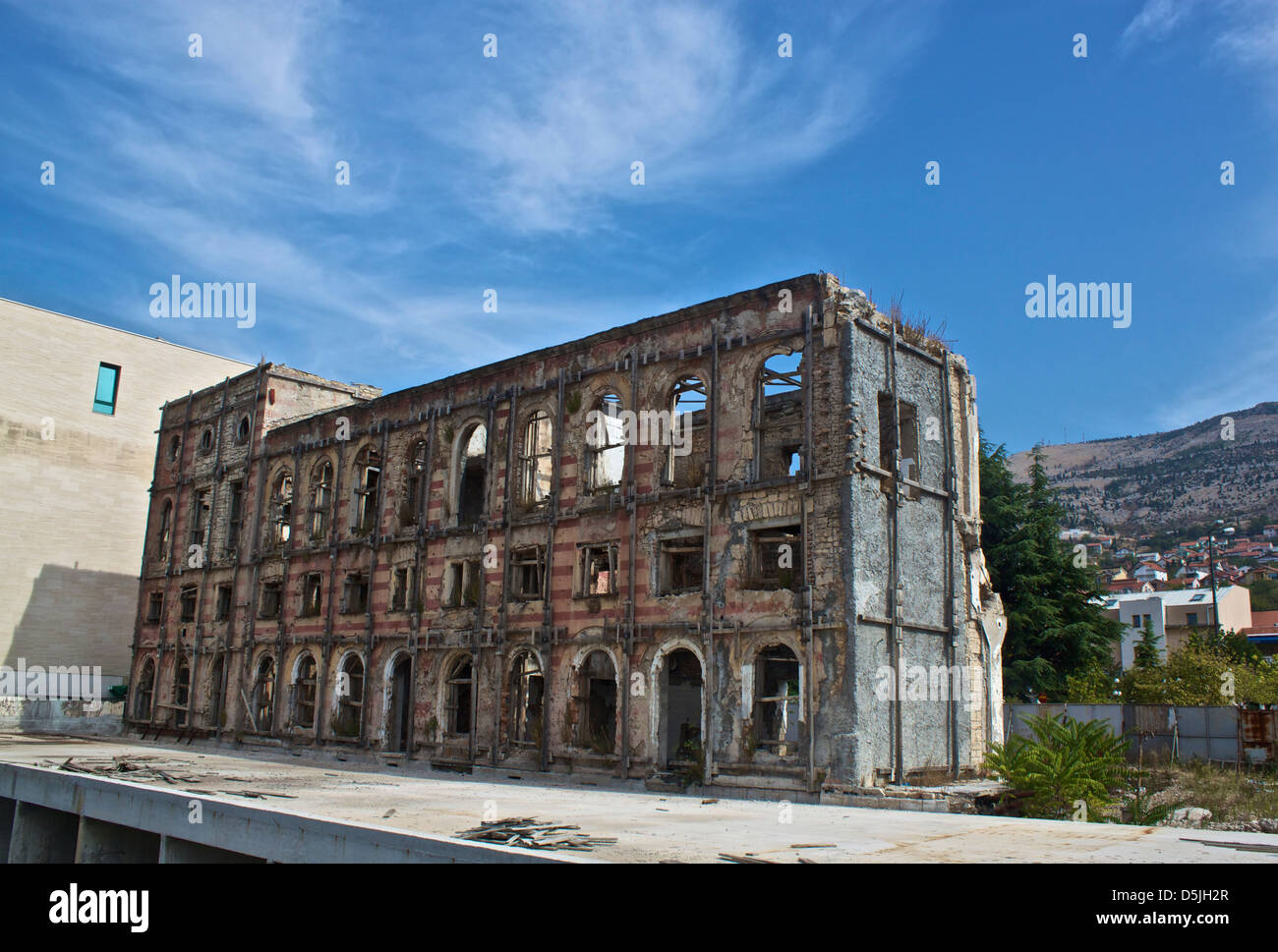 Derelict, abandoned building showing the scars of war in Mostar, Bosnia Stock Photo