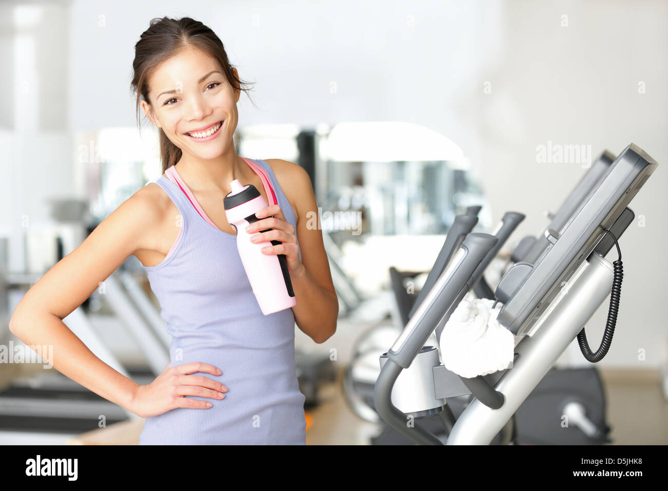 Beautiful young smiling mixed race Caucasian / Chinese Asian woman drinking water standing by moonwalker fitness Stock Photo