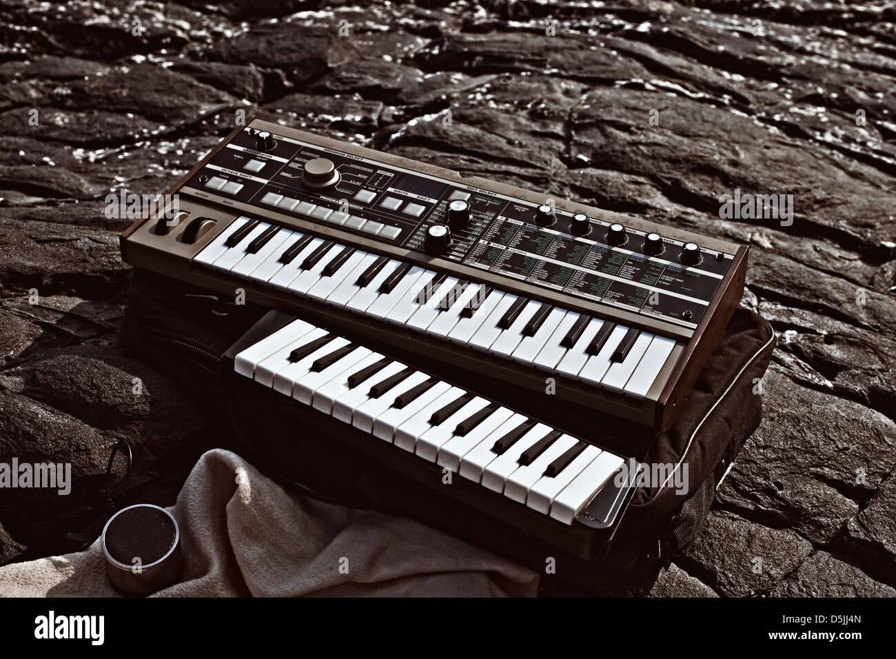 Music synthesizer lying on rocks close up - Stock Image
