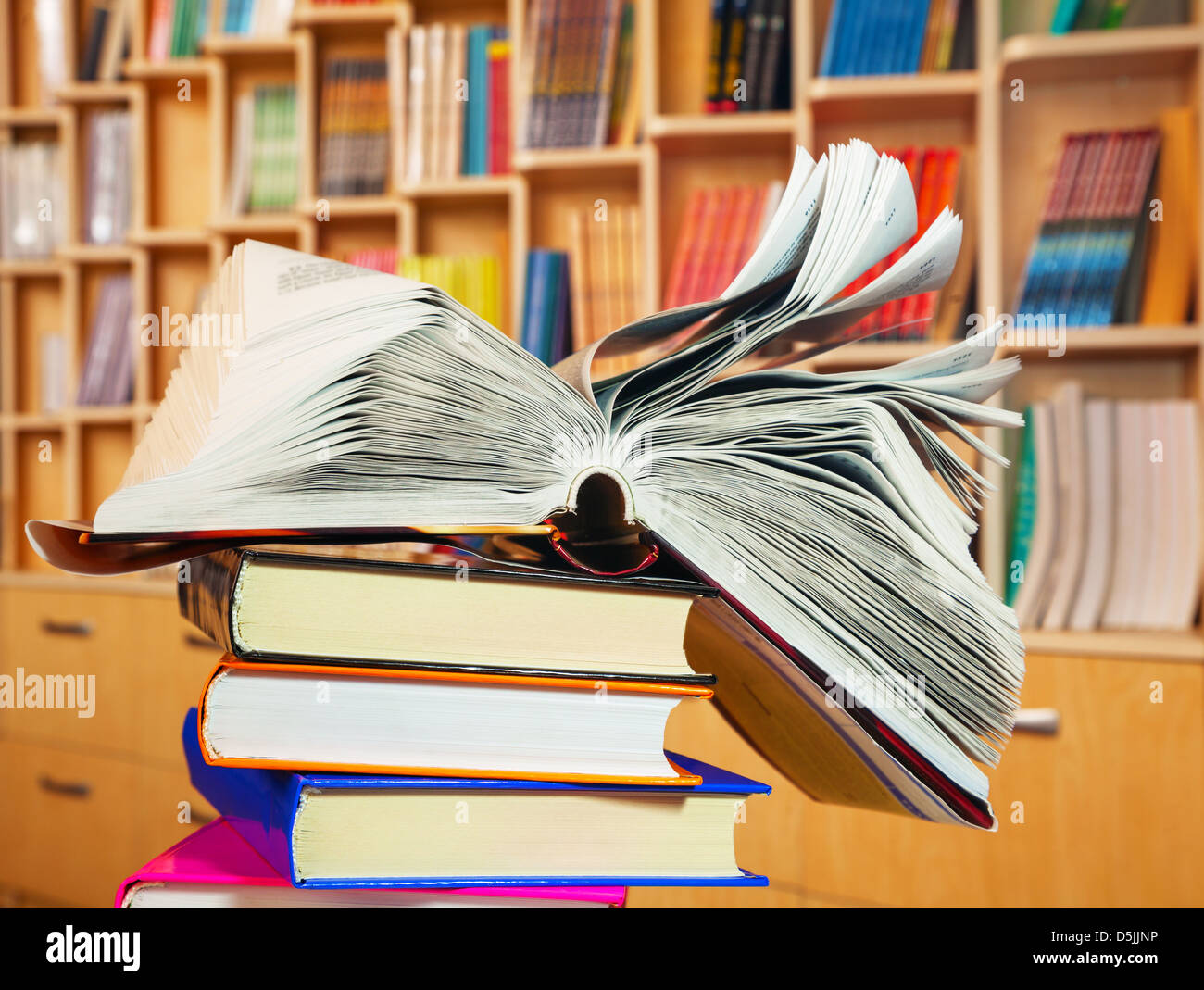 Open book lying on a stack of books - Stock Image