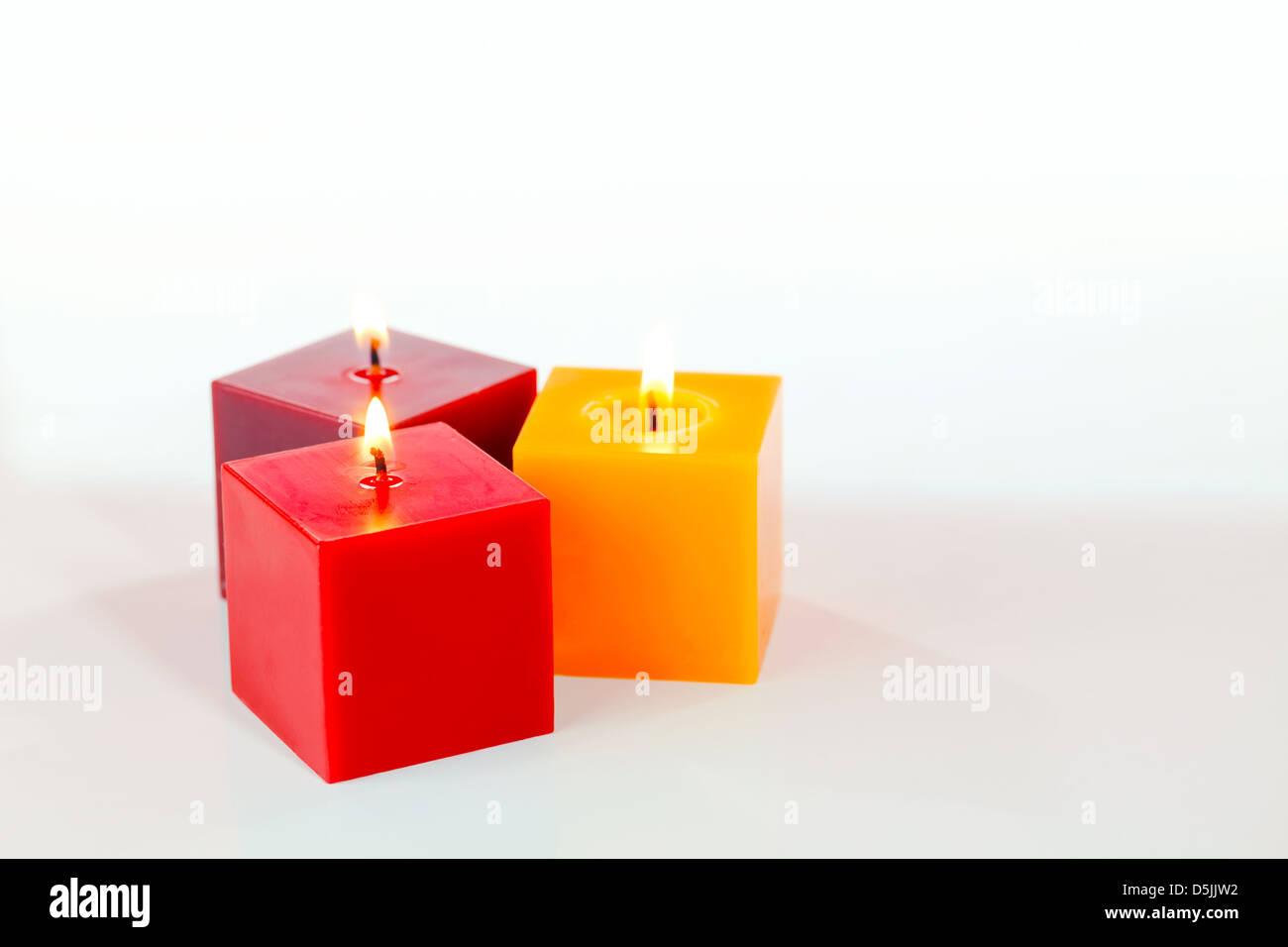 Three burning candles against white background - Stock Image
