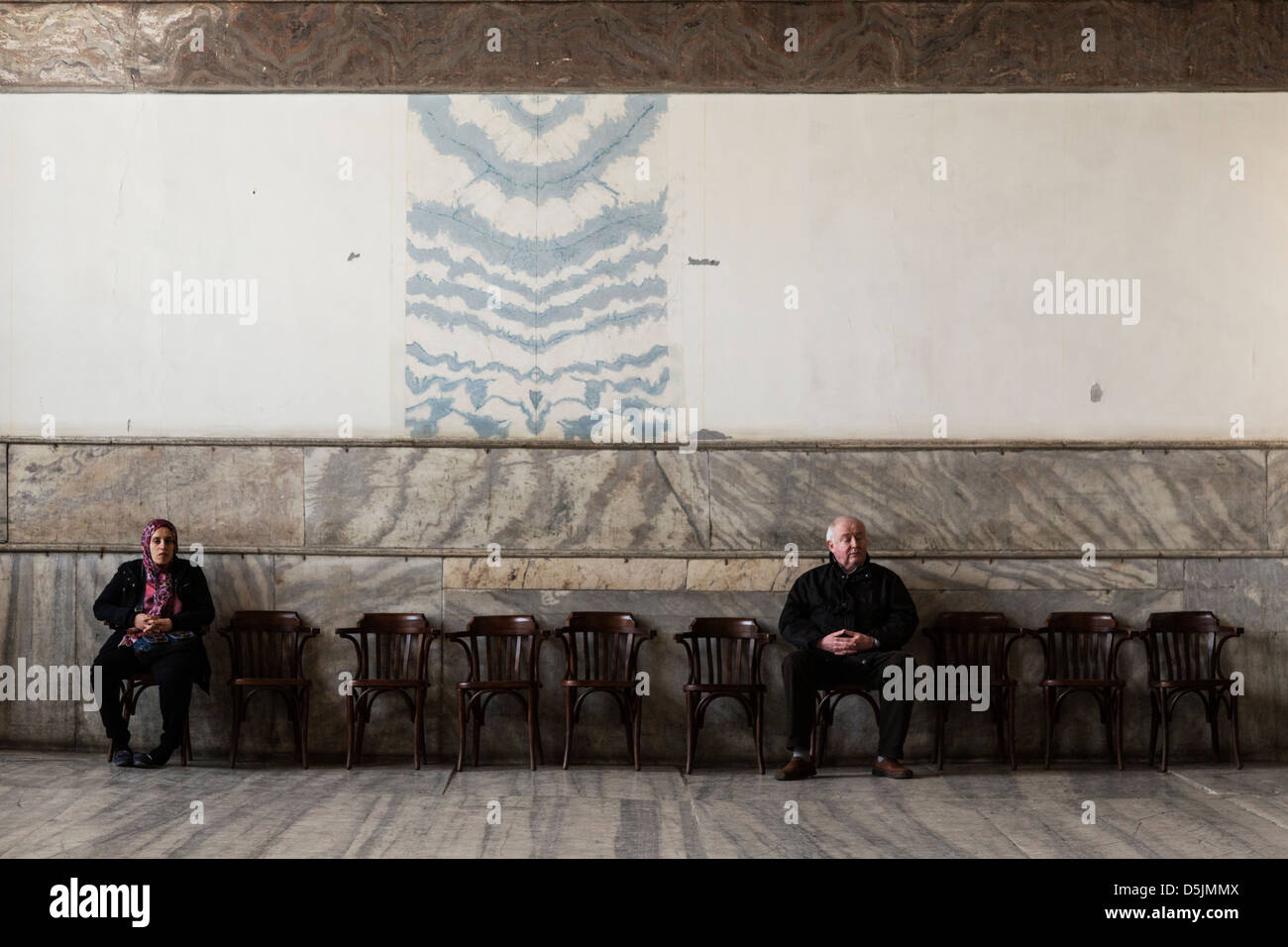 Tourists sit on seats in the Hagia Sophia museum, Istanbul, Turkey. - Stock Image