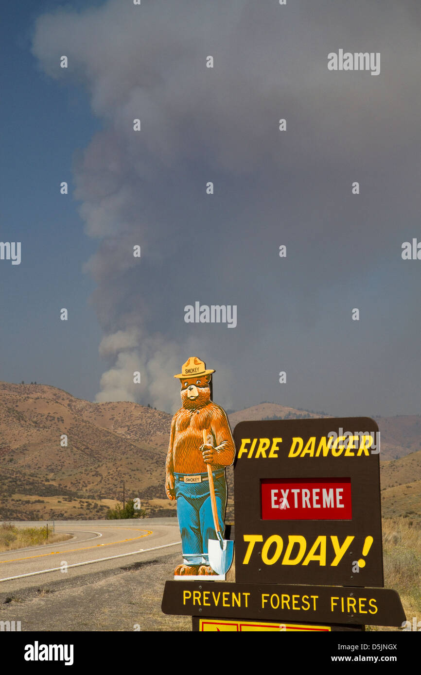 Smokey Bear extreme fire danger sign with a plume of smoke from a forest fire in the background in Boise County, - Stock Image