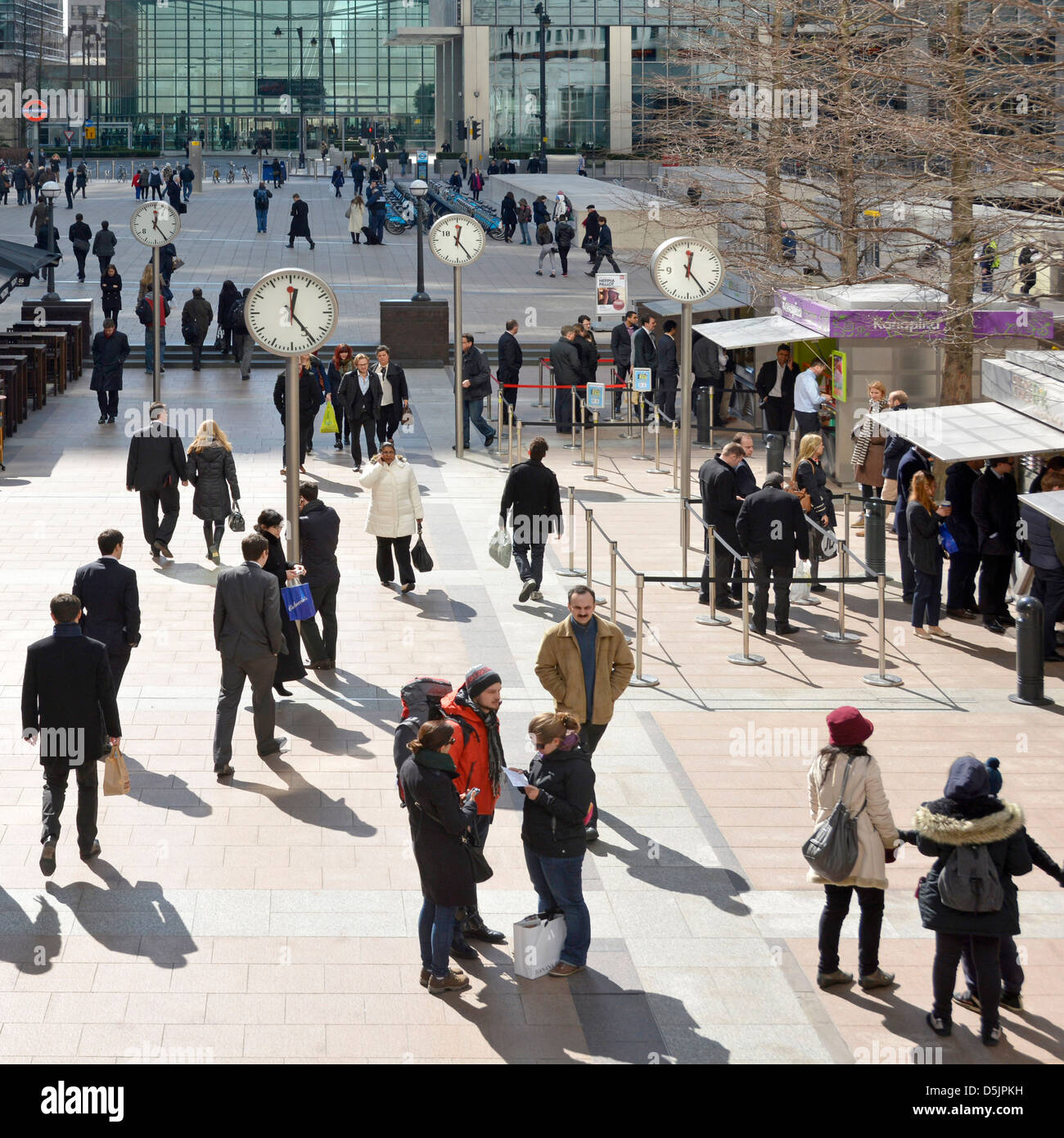Office workers at lunchtime on Canary Wharf plaza with clocks London Docklands Isle of Dogs Tower Hamlets East London - Stock Image