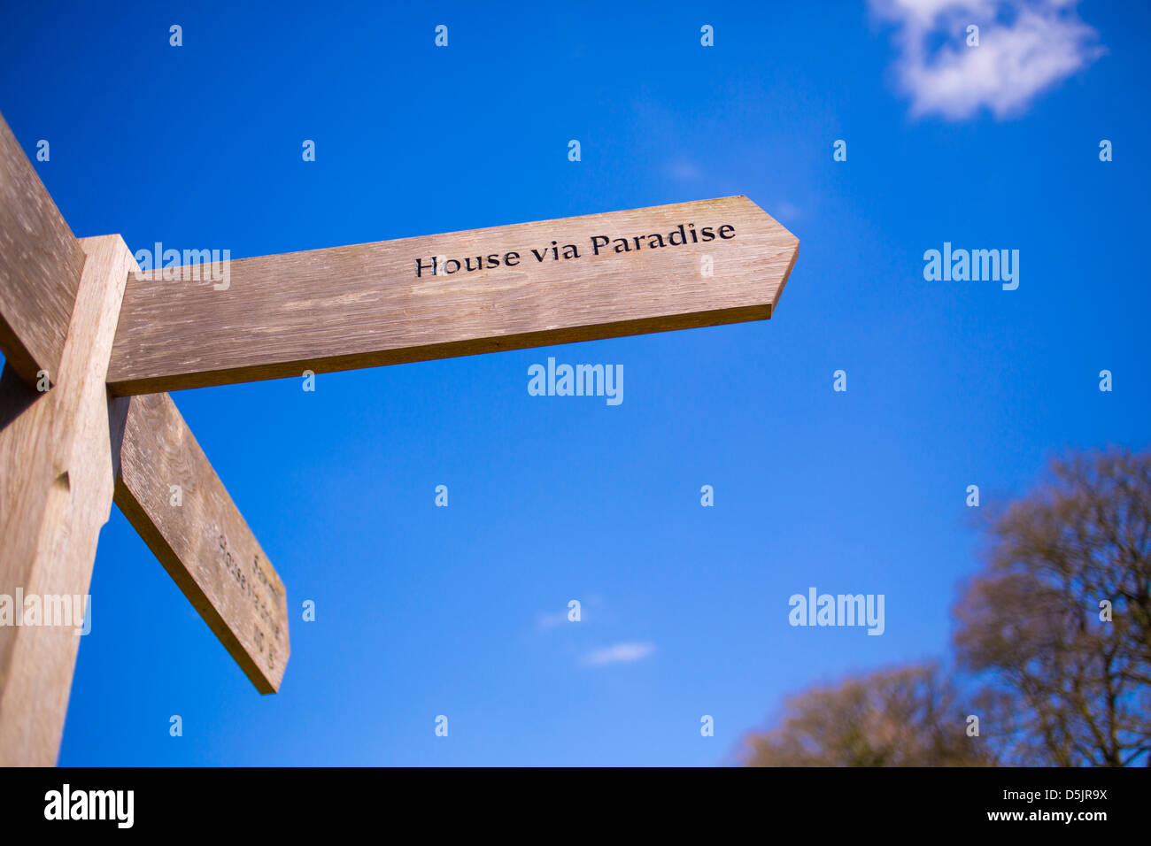 Wooden sign that reads House via Paradise against a deep blue sky on a sunny day. - Stock Image