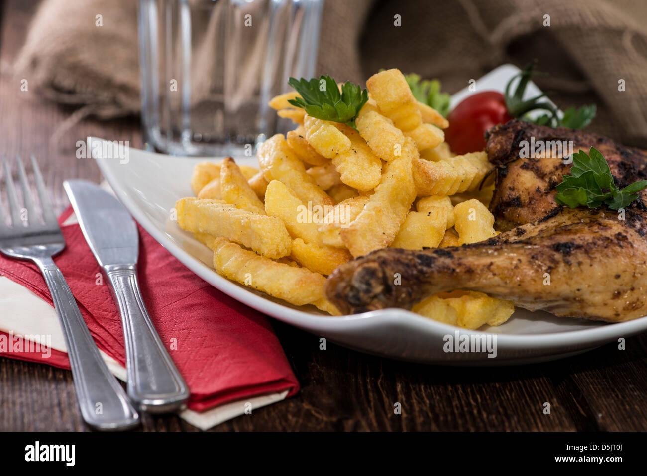 Grilled Chicken legs with Chips on a plate - Stock Image
