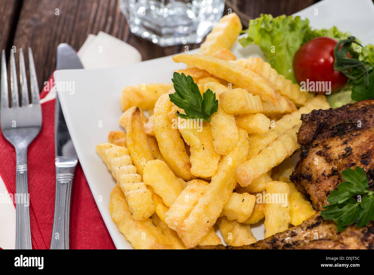 Grilled Chicken with french fries on a plate - Stock Image
