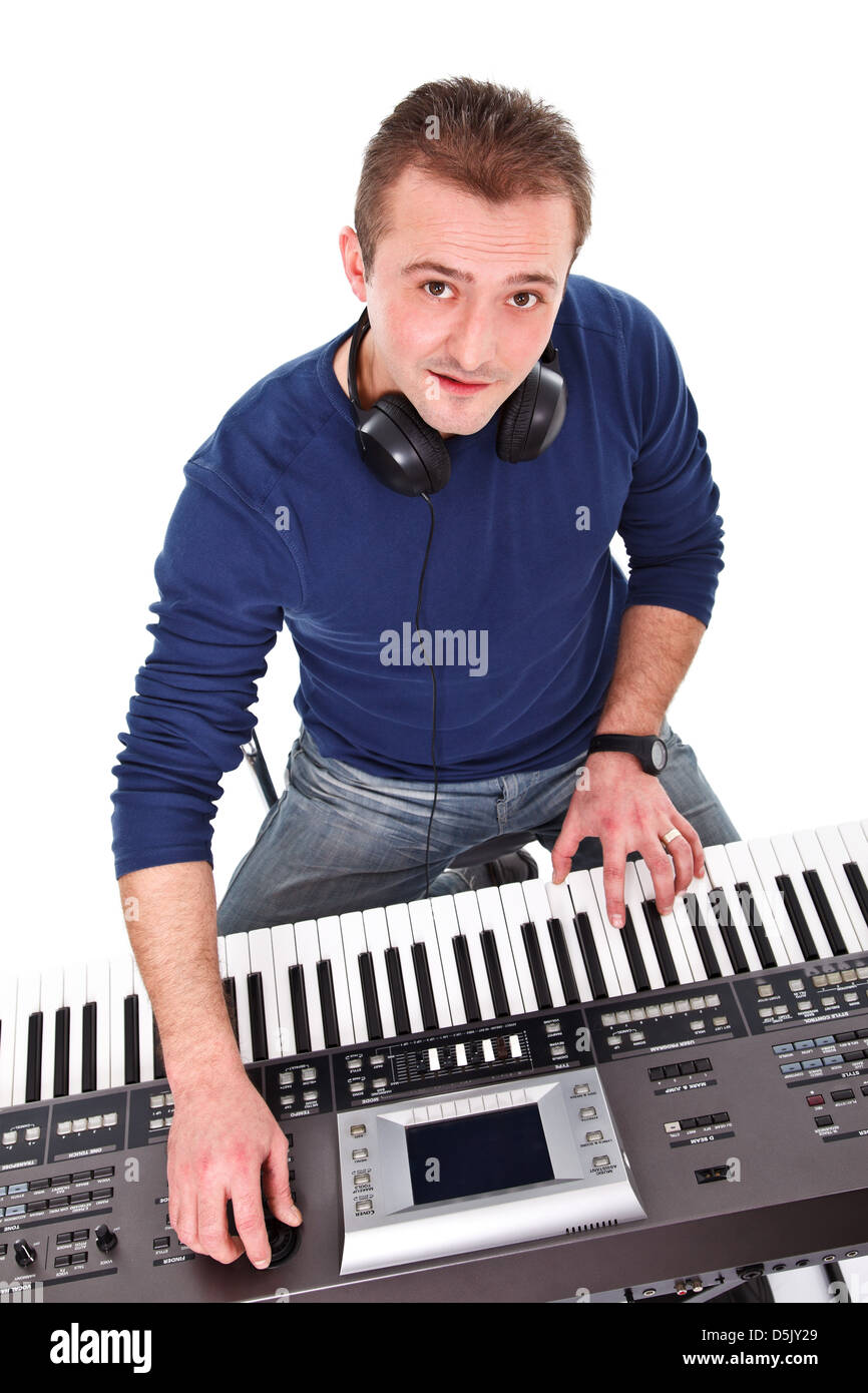 Musician looking at the camera while playing on the keyboard - Stock Image