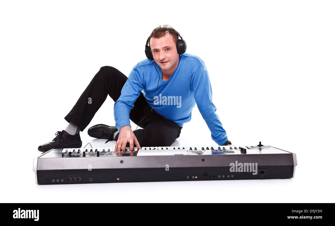Young man posing with synthesizer and headset over white background - Stock Image