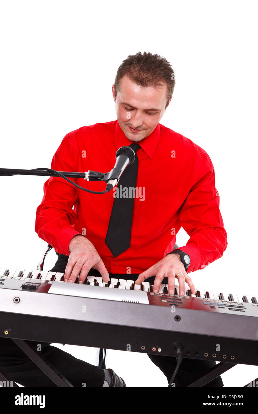 Synthesizer artist in red shirt playing on keyboard behind microphone - Stock Image