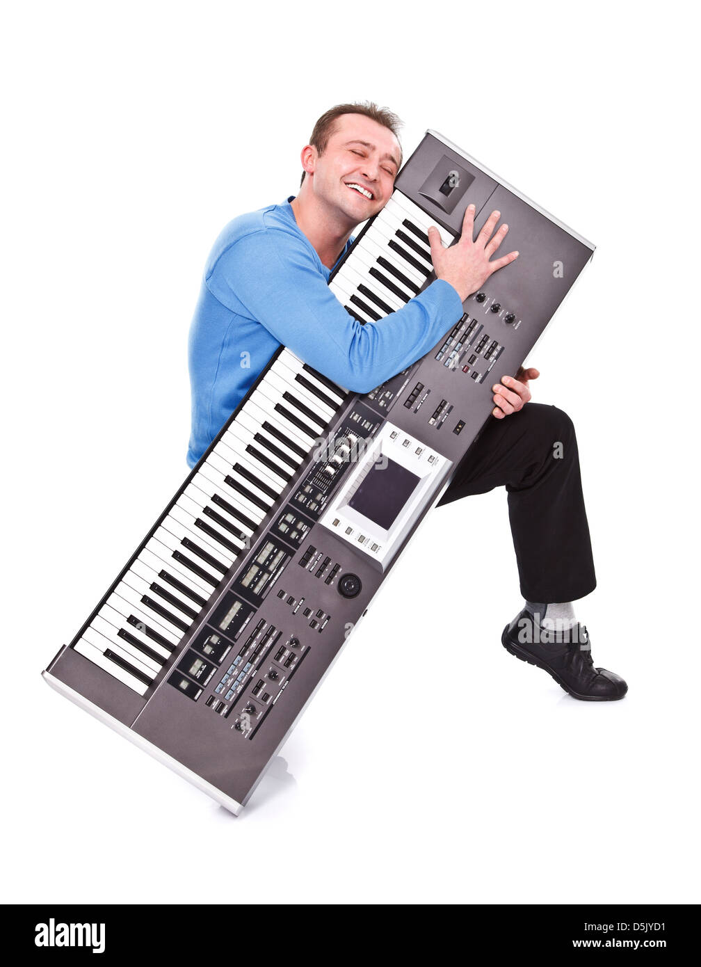 Young man passionately embraces his synthesizer - studio shot - Stock Image