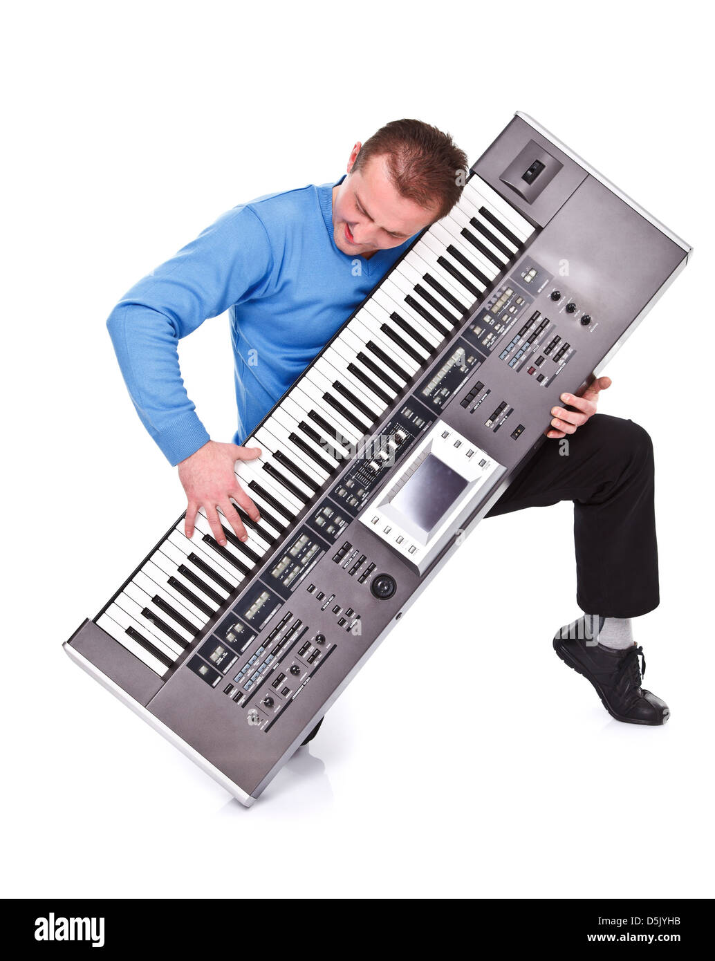 Young man on his knee playing on synthesizer over white background - Stock Image