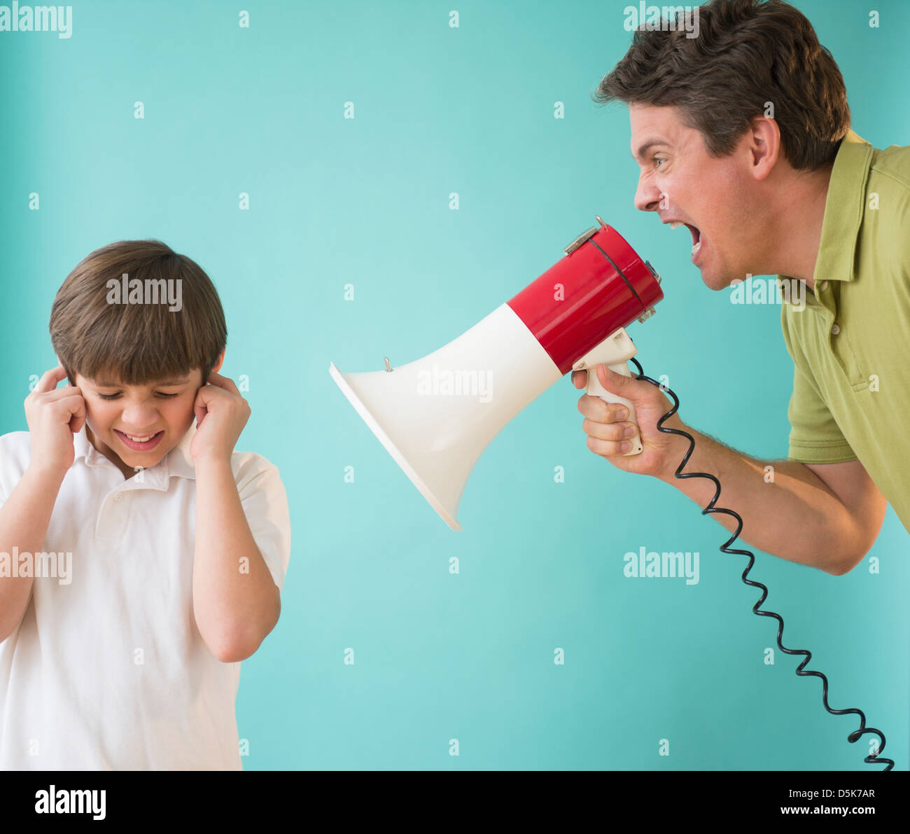 Father with megaphone yelling at son (8-9) - Stock Image
