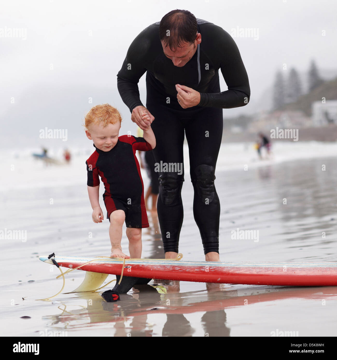 Father and his son (2-3) on beach by surfboard - Stock Image