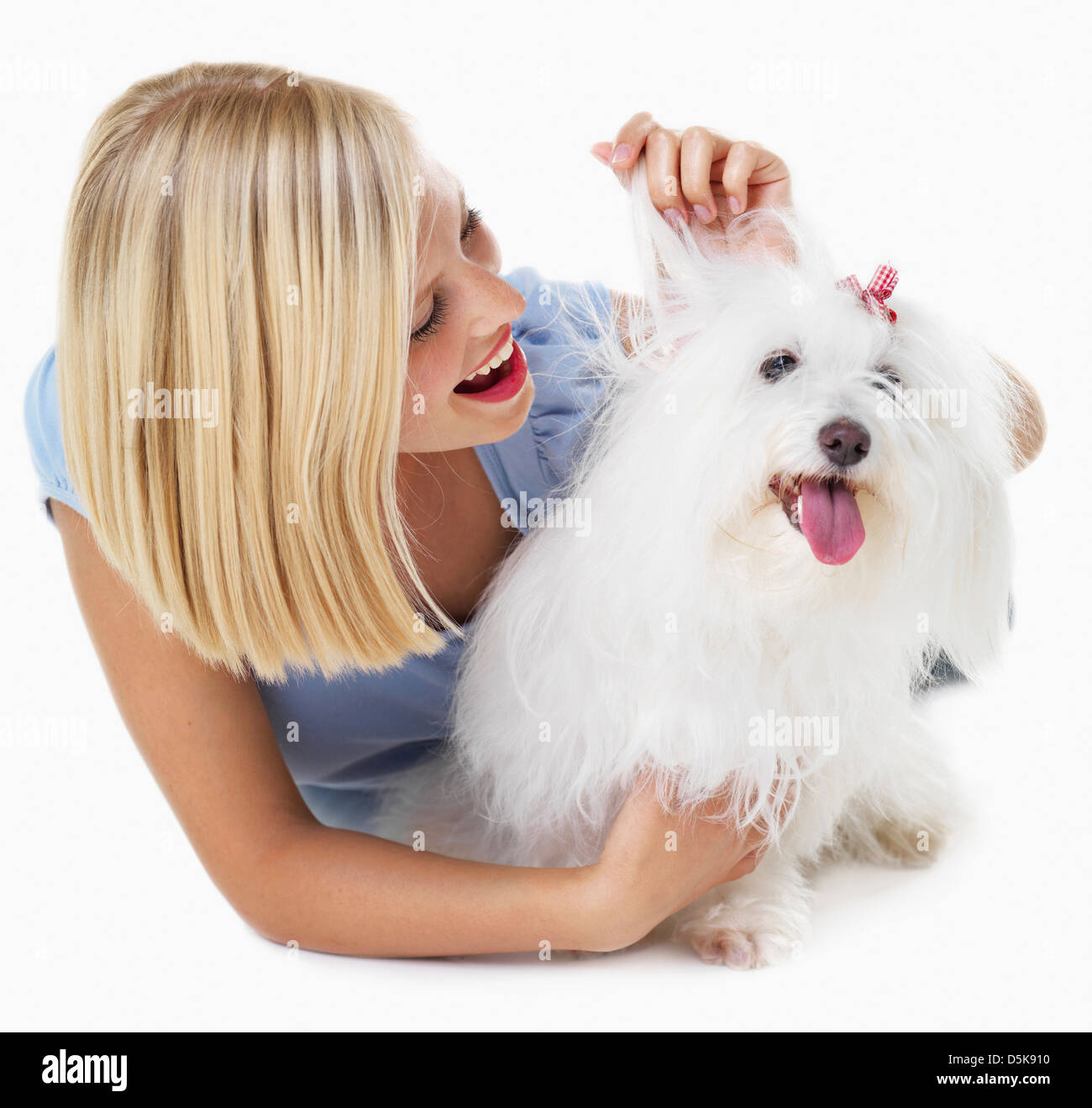 Studio Shot, Portrait of young woman stroking her dog - Stock Image